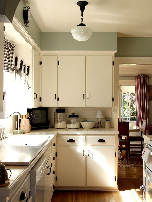 This is almost exactly how my kitchen would look if if we could convince the landlord to let us paint the cabinets white. Same layout, same trim around window, but with crappy linoleum floors and cute yellow and green tile counters.