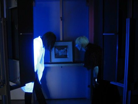 Our conservators studying a painting in UV light
