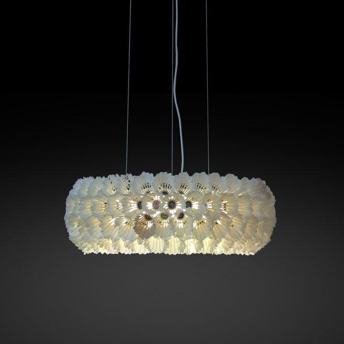 federleicht schwebt dieser einzigartige luster aus gebrauchten federbällen über dem tisch …