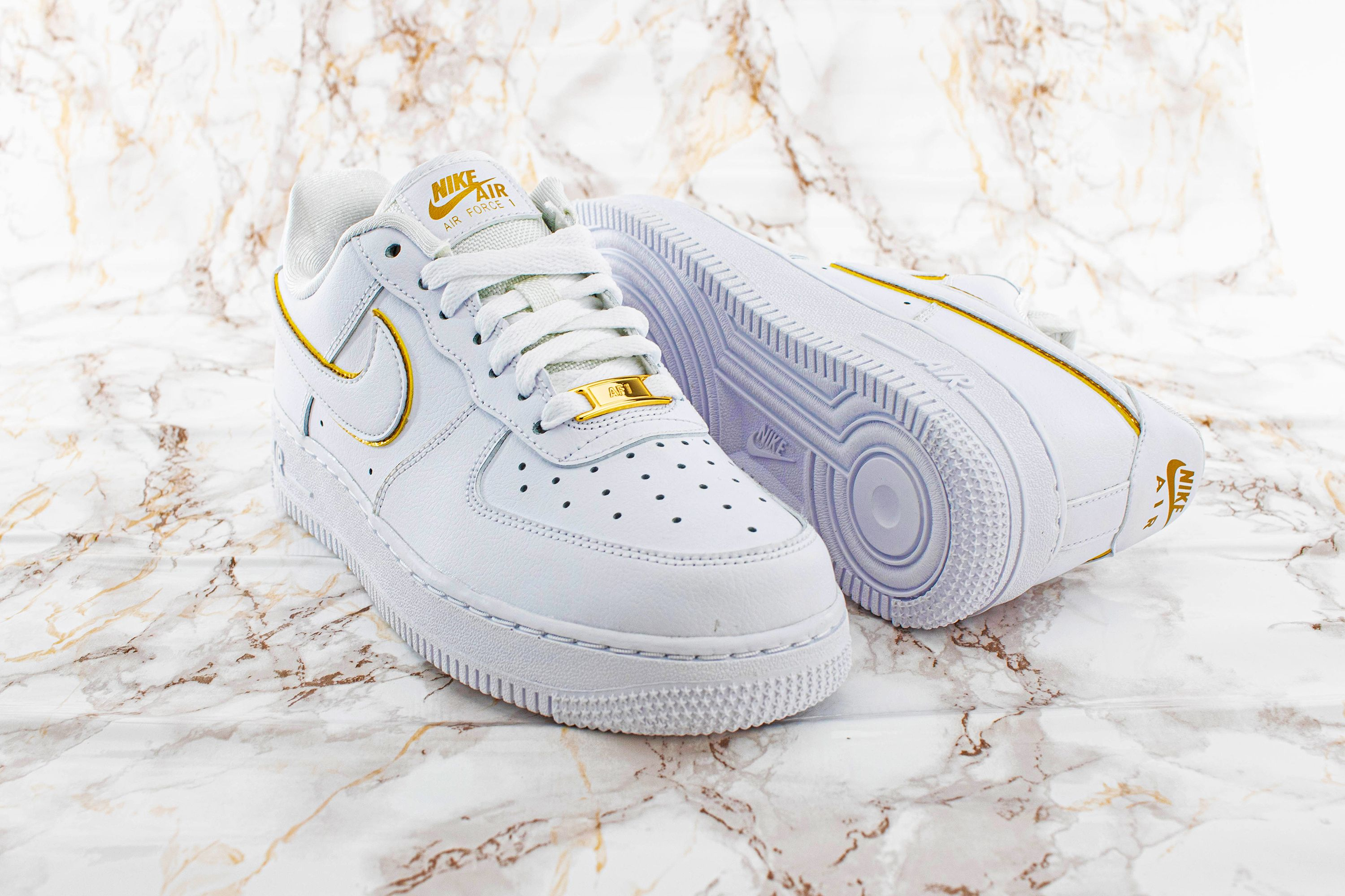 The Nike Air Force 1 07 Essential in white with golden