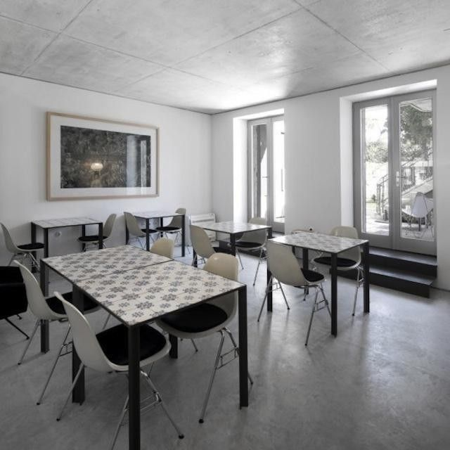 The dining room of Portuguese hotel Casa do Conto features modern steel tables inlaid with traditional Portuguese tile.