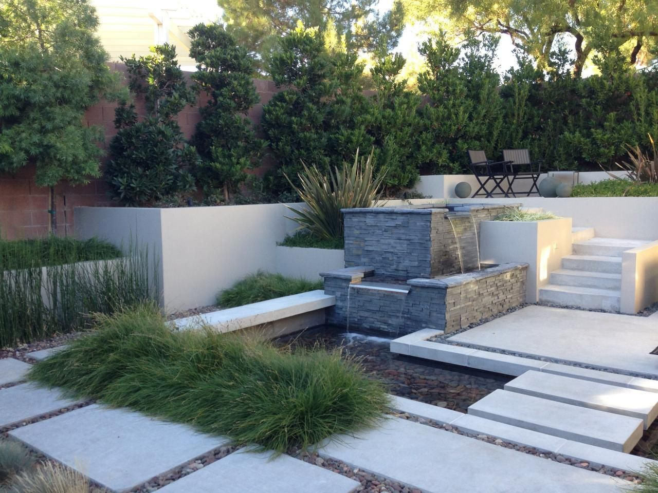 Stacked stone water feature - A Stacked Stone Water Fountain Is The Focal Point In This Backyard Garden