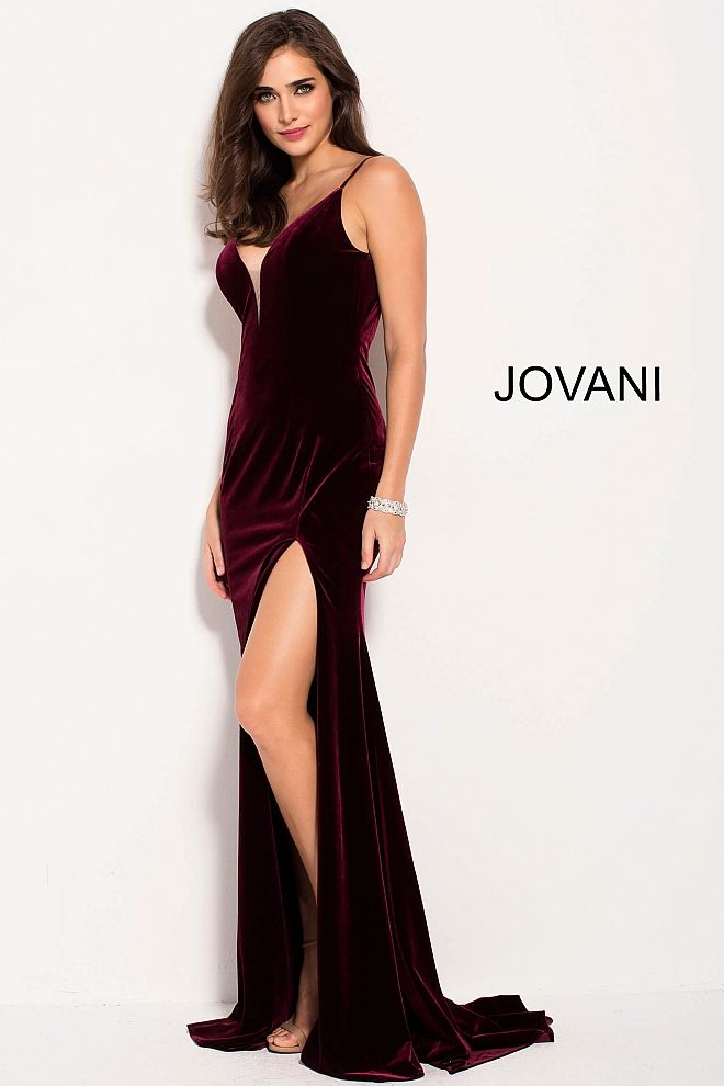 0fe23707bc Floor length form fitting burgundy velvet prom dress with high slit  features sleeveless bodice with spaghetti straps plunging v neck and low  back.