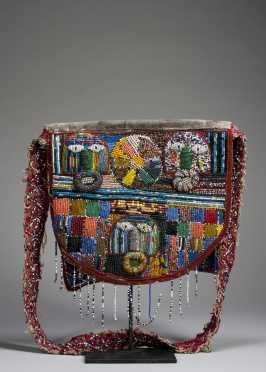 """A fine Yoruba beaded bag:- """"Very finely rendered depicting three faces in two registers; the upper register with two faces separated by a rosette, the lower register with single central face flanked by checkerboard patterns. The sash with beaded designs, fantastic use of color and variety of beads"""""""