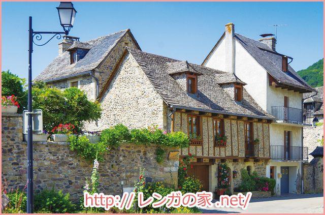 フランスにあるレンガ 石造りの家 外壁に飾られてあるお花や植物が
