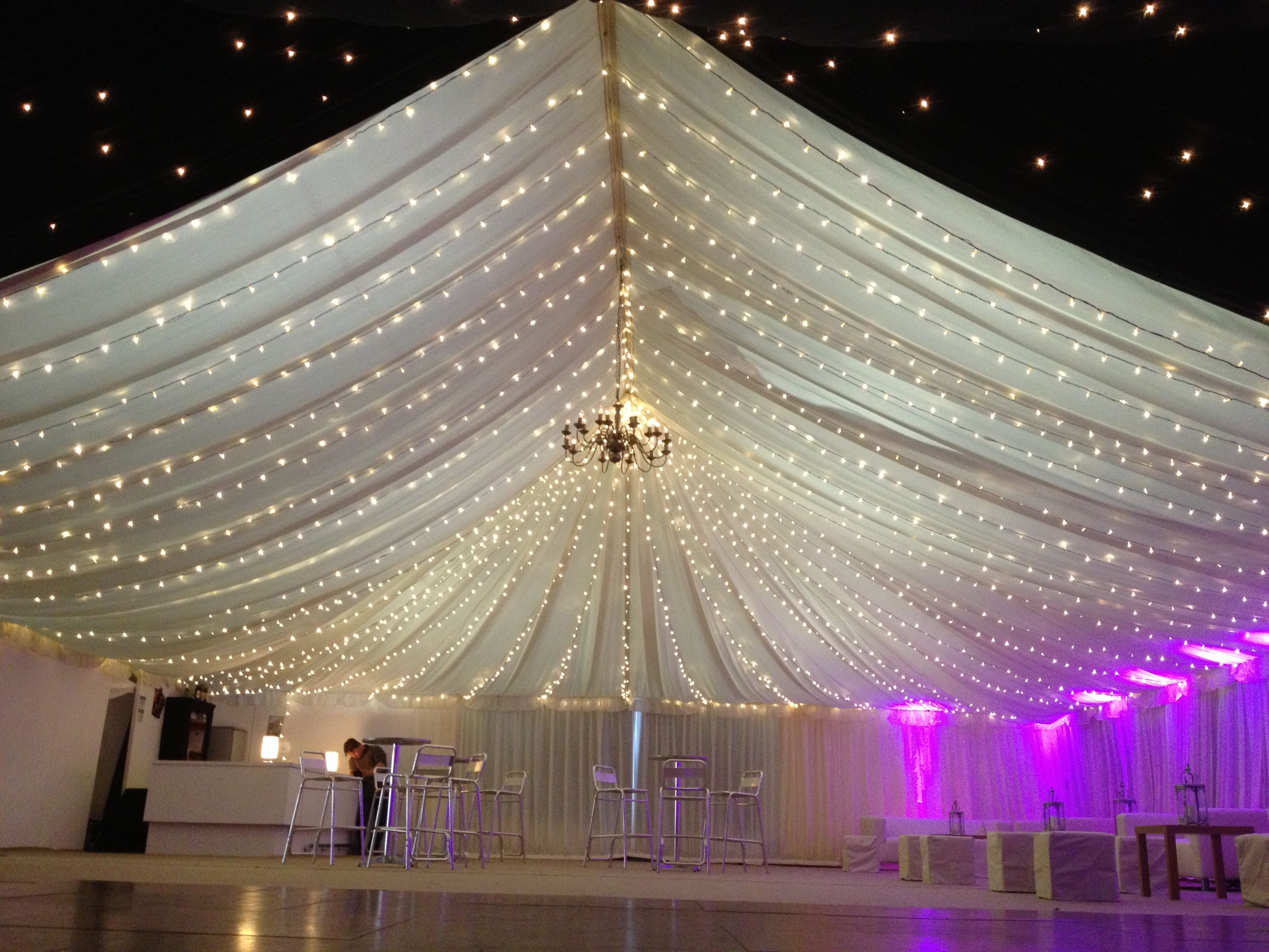 String lighting with up lighters in a marquee