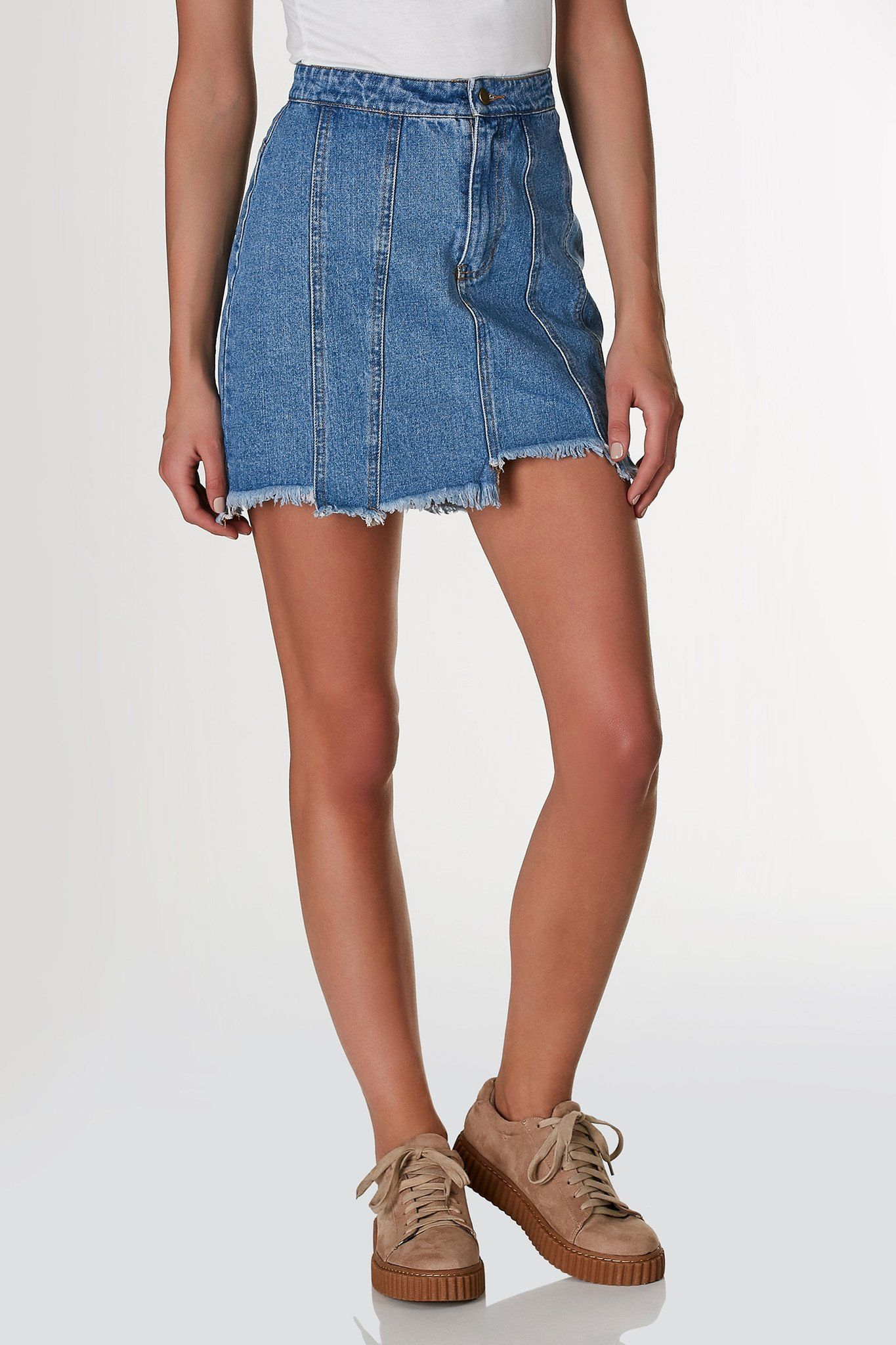 8d4499f47c High rise denim skirt with patched design and uneven raw hem finish. Faux  back pockets for added detail. Each piece is dyed individually and is ...