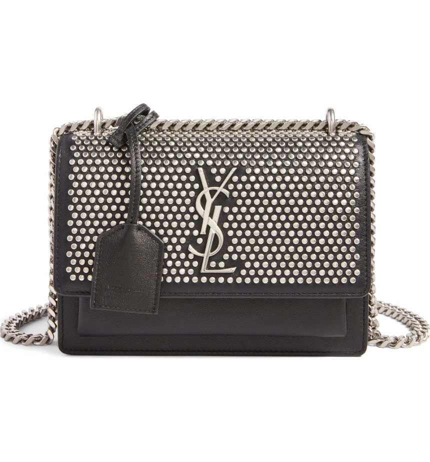 3ca5d13df97 Circular studs, as well as a chain-and-leather strap, give this YSL handbag  enough modern attitude, while a polished insignia and luggage tag keep it  ...