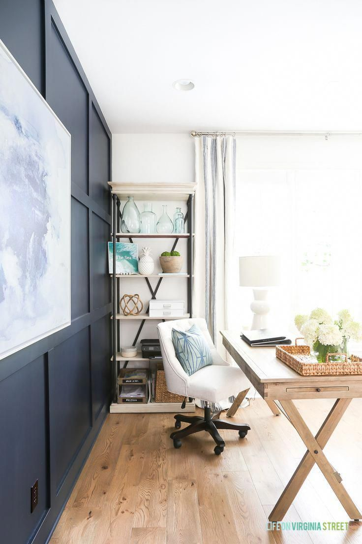 Home office with Benjamin Moore Hale Navy board and batten wall, Simply White walls, navy blue and white abstract artwork, whitewashed bead chandelier, wood desks and Mannington white oak Maison Normandy Bistro hardwood floors. Bookshelf is filled with re #homeofficefurnituretips #halenavybenjaminmoore