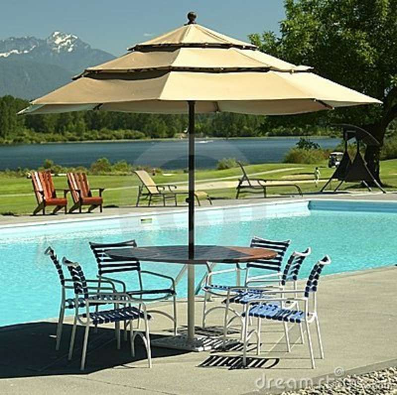 Delightful Outdoor Patio Table By A Pool On A Golf Course