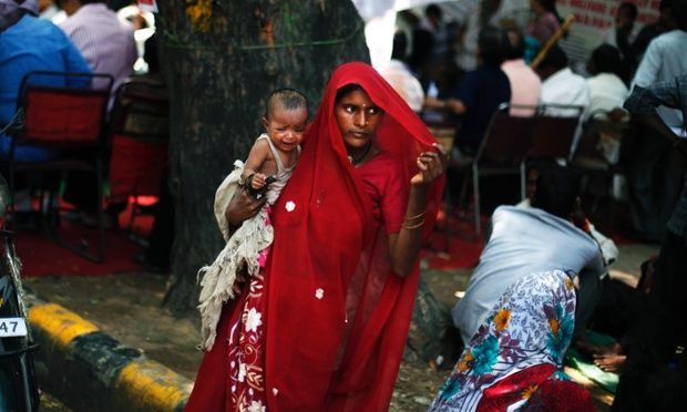 A protester holds her baby as members of India's landless, poor farmers and the tribal community protest in New Delhi, India. The farmers were protesting against the government procuring land for setting up industries and not providing enough subsidy to farmers among several other grievances.