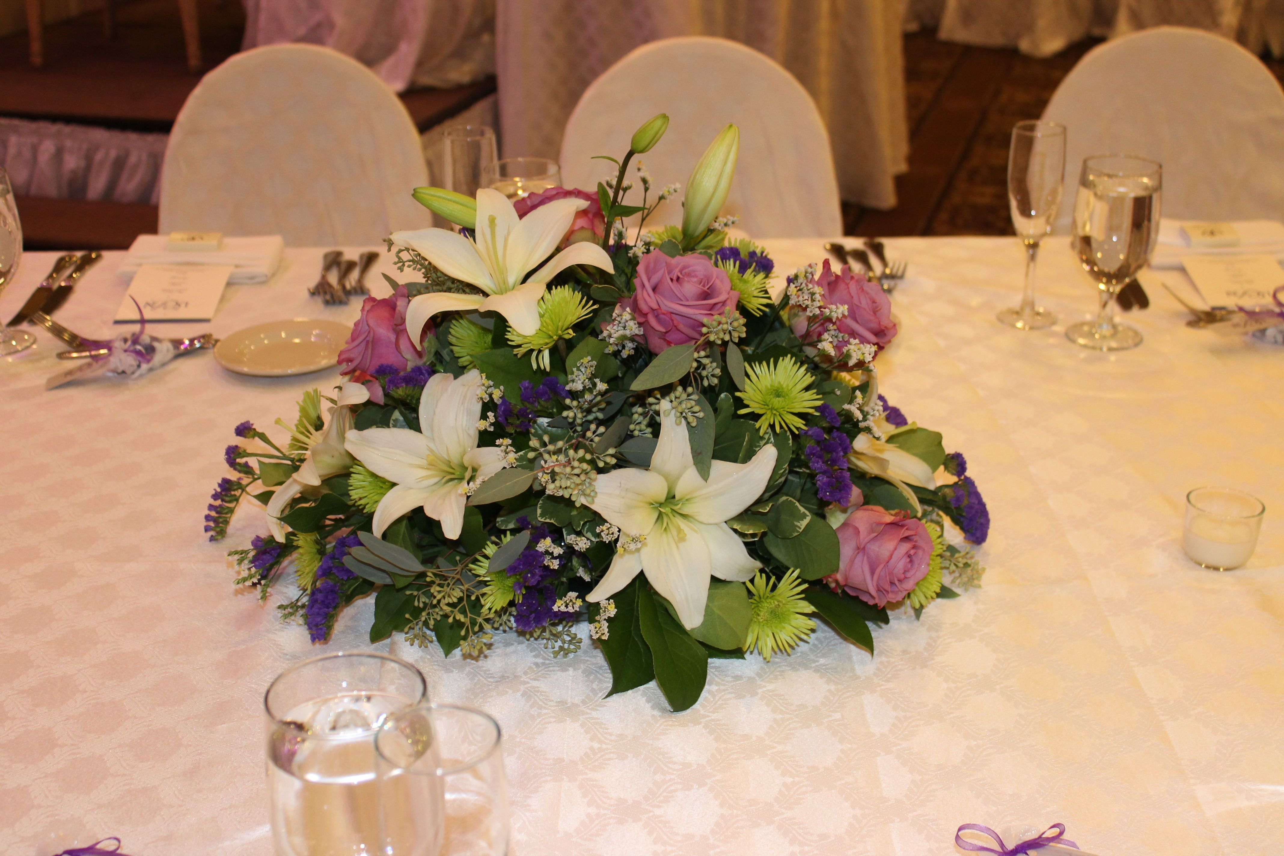 Wedding centerpiece of white lilies, purple roses, eucalyptus and green buttons