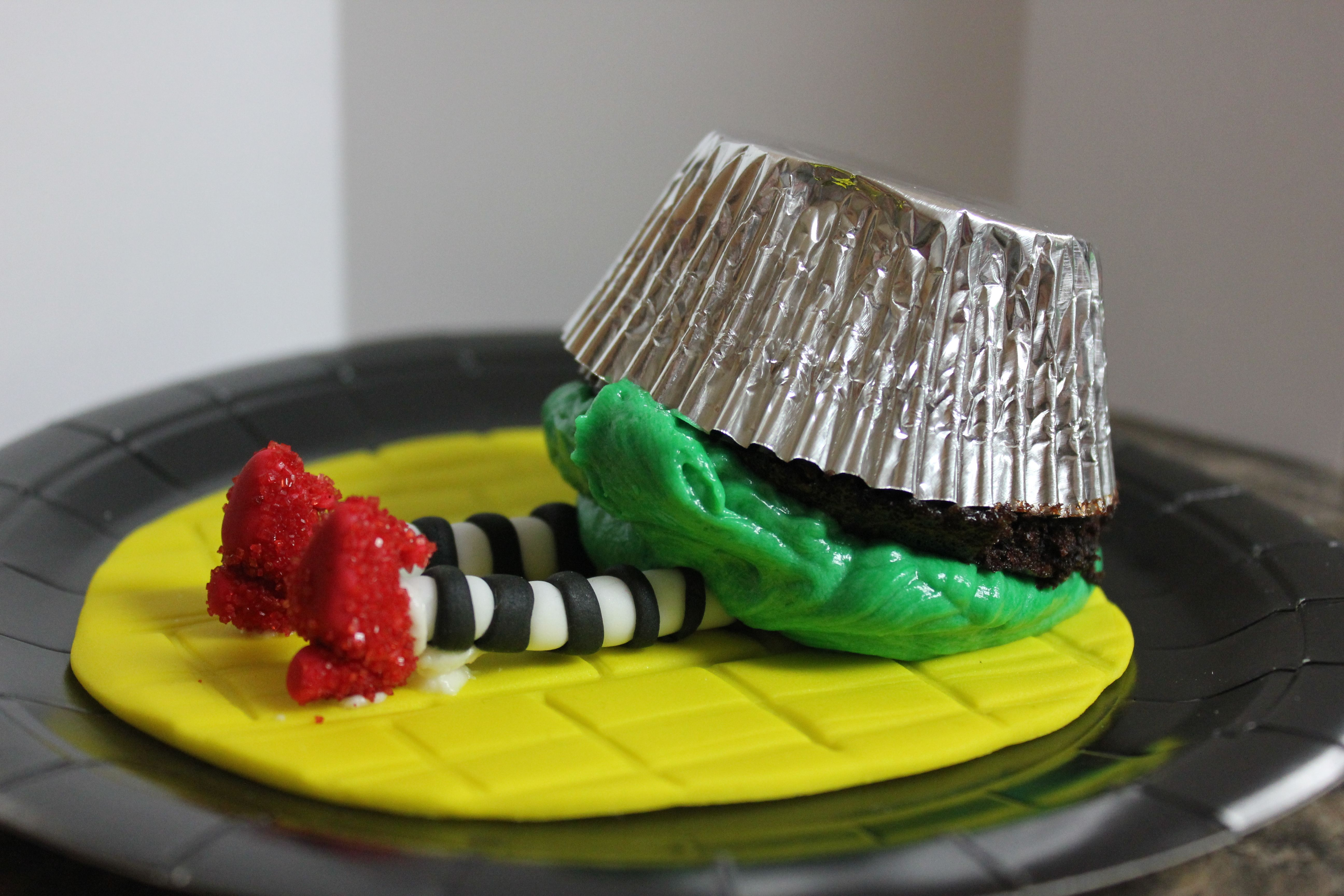 Wicked witch of the East; Fondant Ruby slippers covered in sugar, fondant legs and yellow brick road, butter cream frosting.