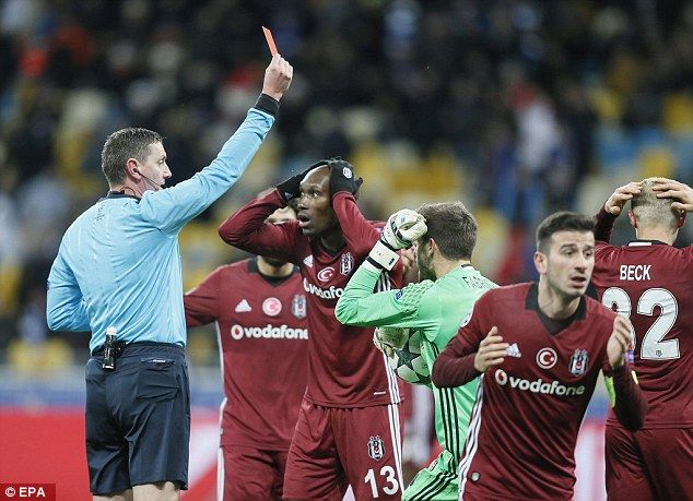 Referee Craig Thomson (left) shows the red card to Andreas Beck of Besiktas (right)