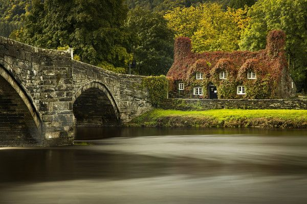 A neutral density filter and a long exposure were used to create this image.) During a break from the rain of Storm Aileen, the leaves of the Virginia creeper begin to take on their Autumn colour at the Tu Hwnt i'r Bont tea room on the banks of the River Conwy at Llanrwst in north Wales on September 13, 2017 in Llandudno, Wales. The cottage named Tu Hwnt i'r Bont (Beyond the Bridge) was built in 1480 and has become a magnet for phtographers and tourists from across the world during Autumn.