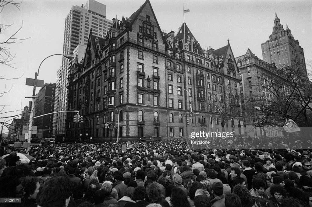 Crowds gathering outside the home of John Lennon in New York after the news that he had been shot and killed. A flag flies at half-mast over the building.
