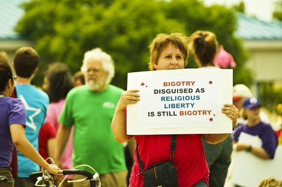 Protester holding up sign: bigotry disguised as religious freedom is still bigotry.