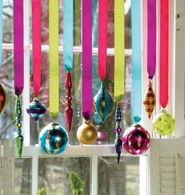 Ornaments Hung by a window try with gold and silver and bronze ornaments and cream ribbon - windows on either side dining table