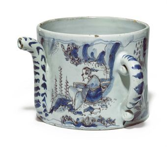 A LONDON DELFT POSSET-POT  CIRCA 1680  Of cylindrical form with typical spout, flanked by C-scroll handles, trekked in manganese and painted in shades of blue with Chinoiserie figures in rockwork landscapes