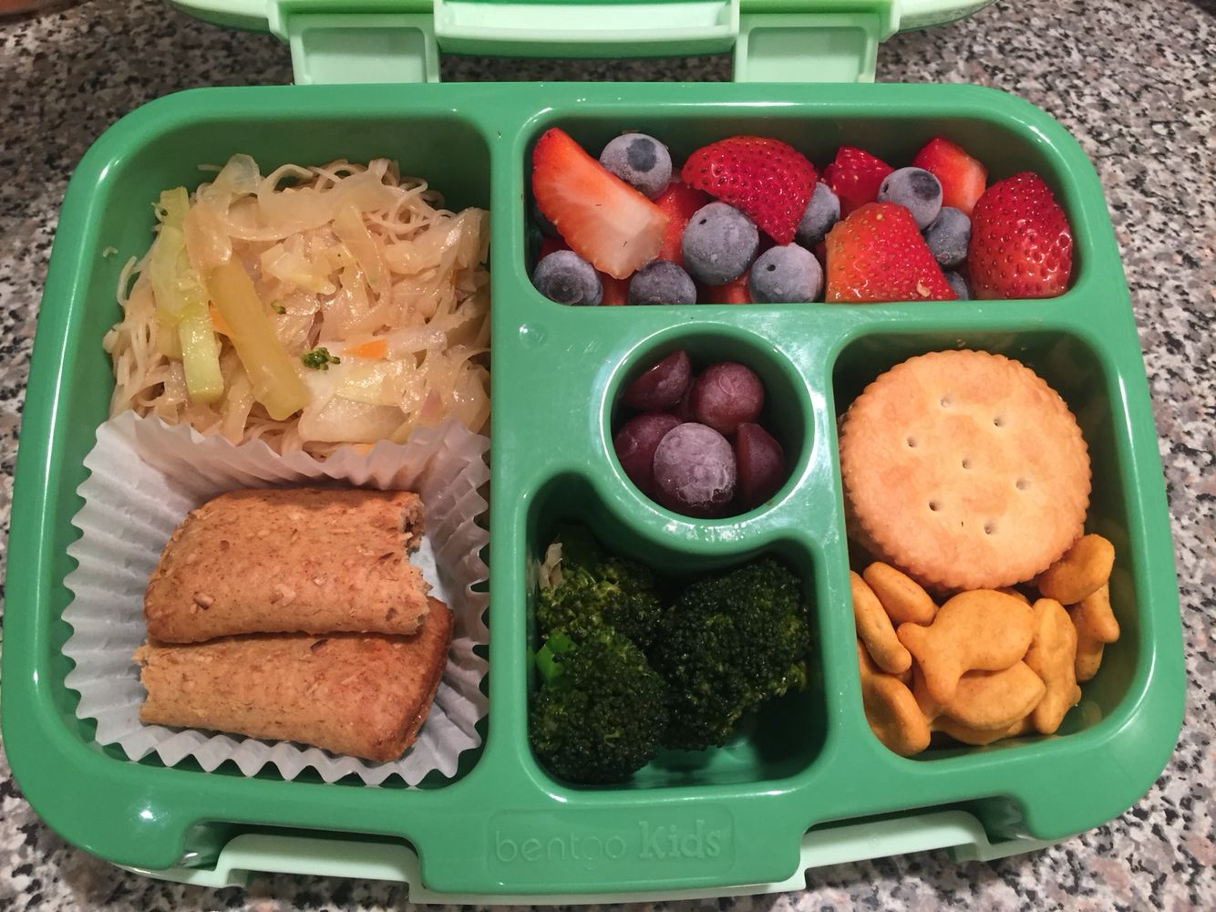 Rice noodles stir fry, Nutrigrain  bar, broccoli, crackers, goldfish, frozen grapes, strawberries and blueberries.