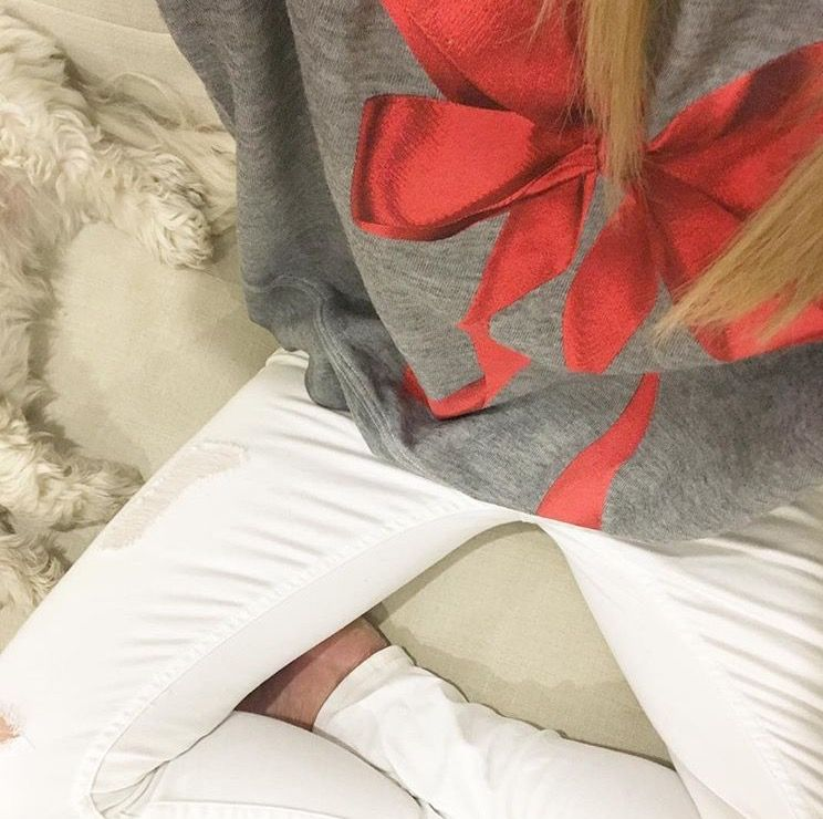 bow-sweatshirt-white-denim-sitting-on-couch-with-with-puppy http://styledamerican.com/latest-roundup/
