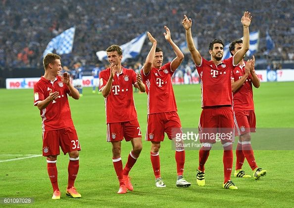 The Bayern Munich players celebrate victory with their supporters during the Bundesliga match between FC Schalke 04 and Bayern Muenchen at...