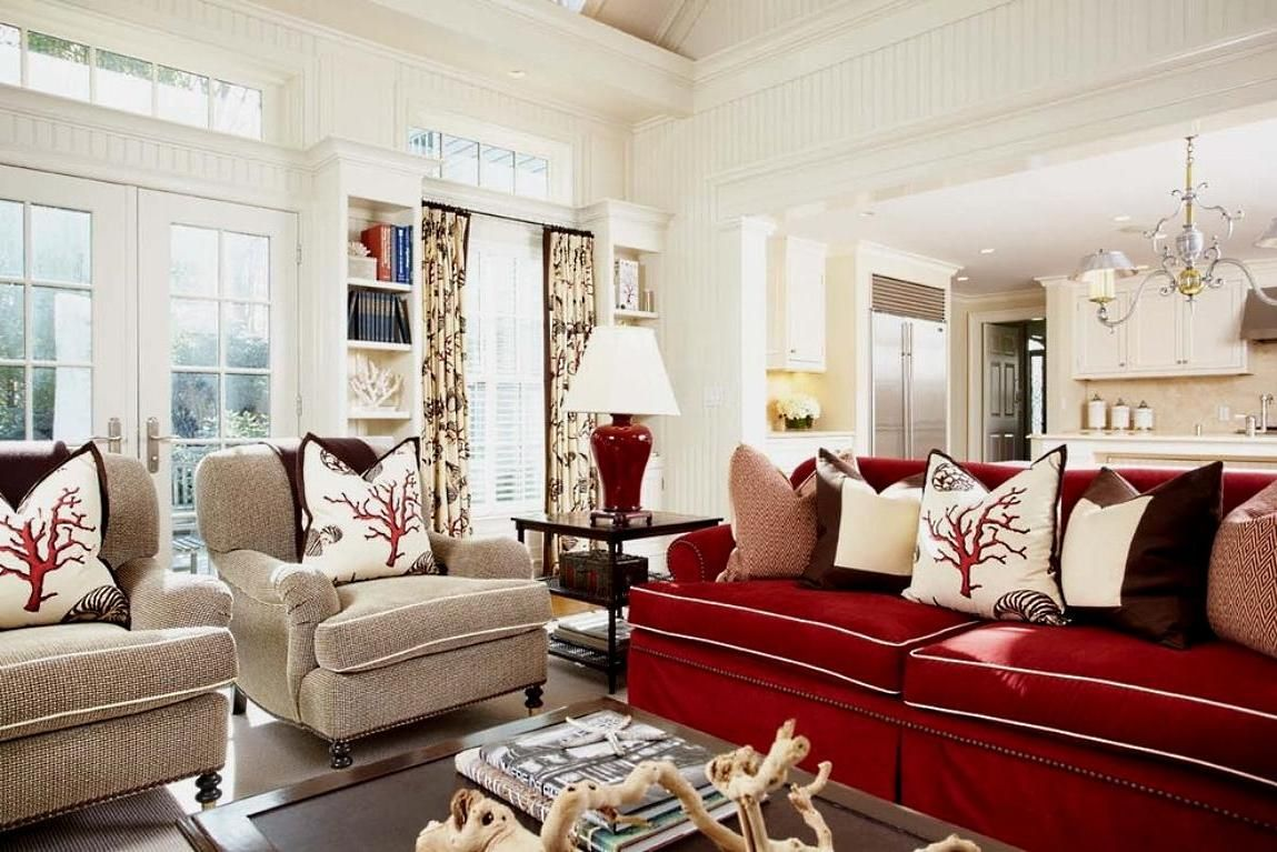 Scarlet sofa and fabric armchairs with small pillows in a ...