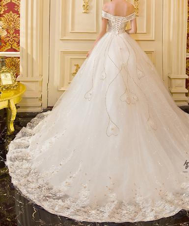 فستان زفاف أبيض بأكتاف منخفضة مزين بفصوص من الكرستال الذهبي متركز على منطقة الصدر ومتفرق على أنحاء الفستان تحت منطقة Dresses Wedding Dresses Formal Dresses