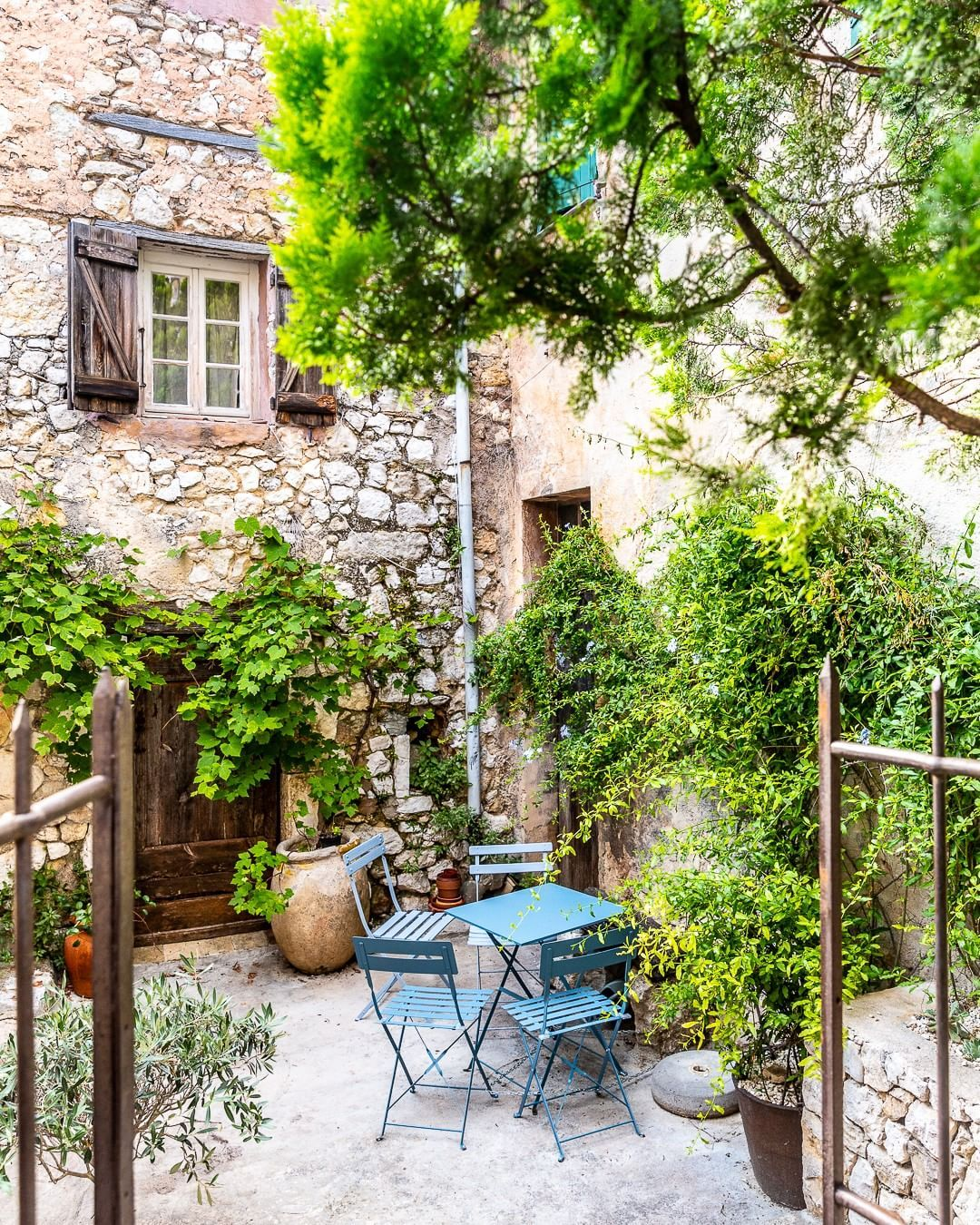 A medieval courtyard with blue patio furniture in the ...