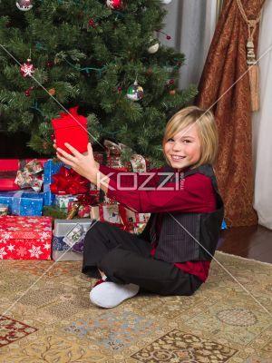 portrait of a cheerful boy holding his christmas gift. - Portrait of a cheerful boy holding his christmas gift while sitting near christmas tree, Model: Josh Chapman