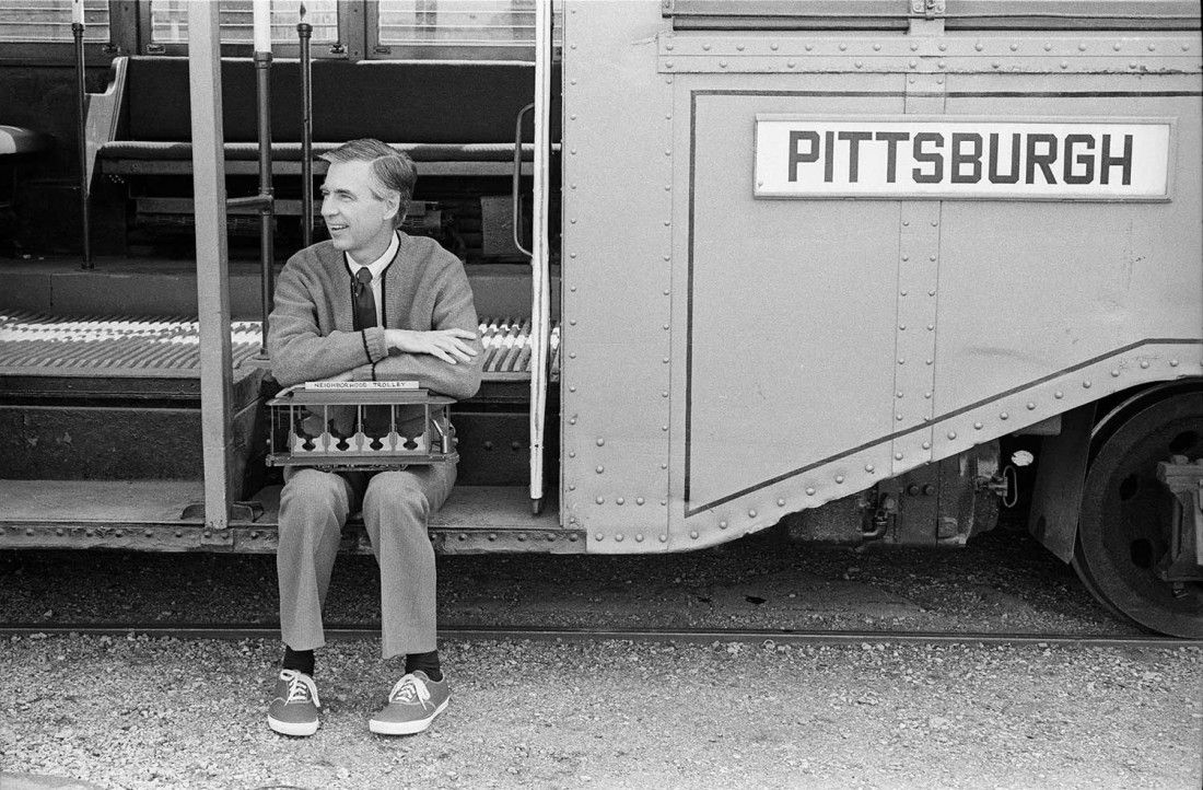 Fred Rogers sits on a trolley that reads