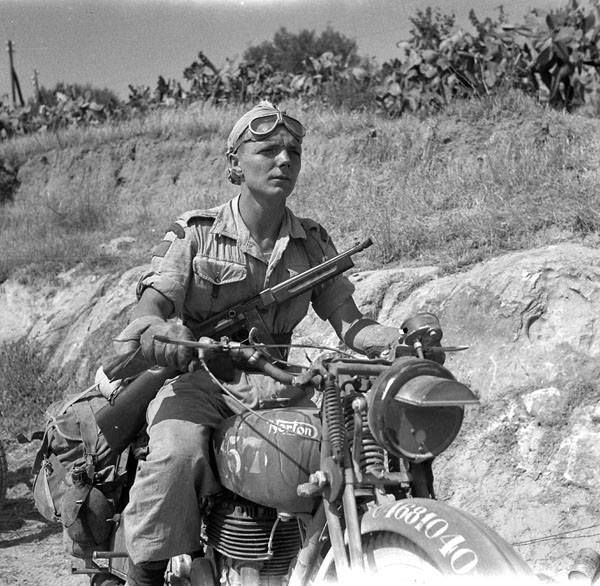 Dispatch rider, Private H. McDowell of the 48th Highlanders of Canada strikes a pose for the photographer on a Norton 16H motorcycle. At the time the photographer stopped him, he was delivering a message to the regiment's advanced headquarters, in Regalbuto, Italy, 1943. McDowell carries a 0.45 caliber Thompson submachine gun