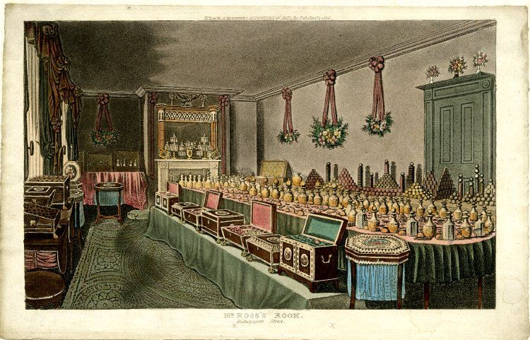 Interior of the shop of Alex Ross, perfumer in London; a large table displays the many perfume bottles and scents on offer, wooden chests on bench  next to table contain further goods; garlands of flowers hang from walls; illustration to Ackermann's 'Repository of Arts'