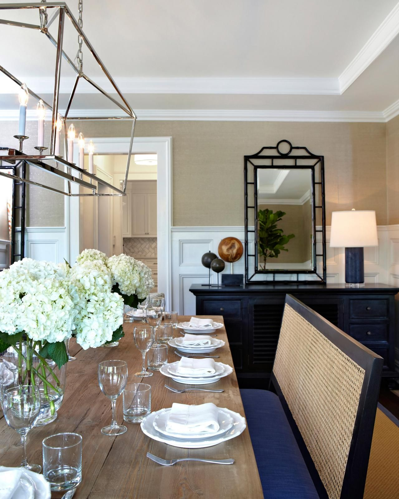 A hand-carved solid birch mirror in a black finish hangs above an ebony hand-rubbed buffet table, drawing the eye up to visually heighten this neutral dining room. A modern polished nickel chandelier illuminates the crisp, clean table settings in the neutral space. White dinnerware complements the white wainscoting and tray ceiling, while clear glass vases hold fresh hydrangea bloom centerpieces.