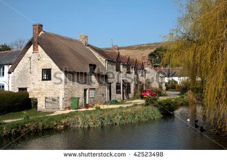 Traditional, British, picturesque village in Dorset, England with pond, ducks and vintage buildings on a sunny day. - stock photo