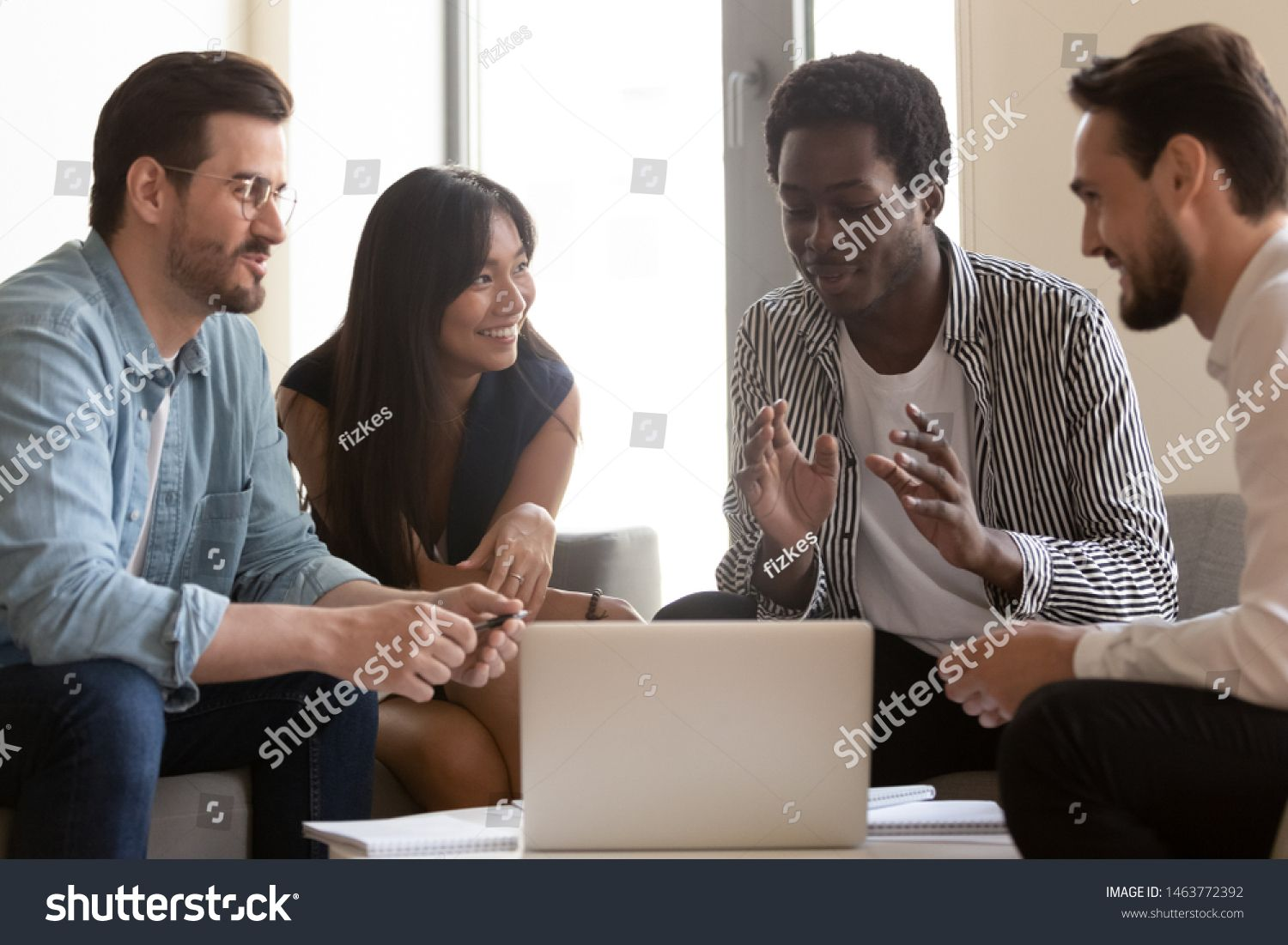 Multiethnic business team listen to african leader mentor coach explain online strategy with laptop diverse workers group brainstorm talking gathered in office work toget...