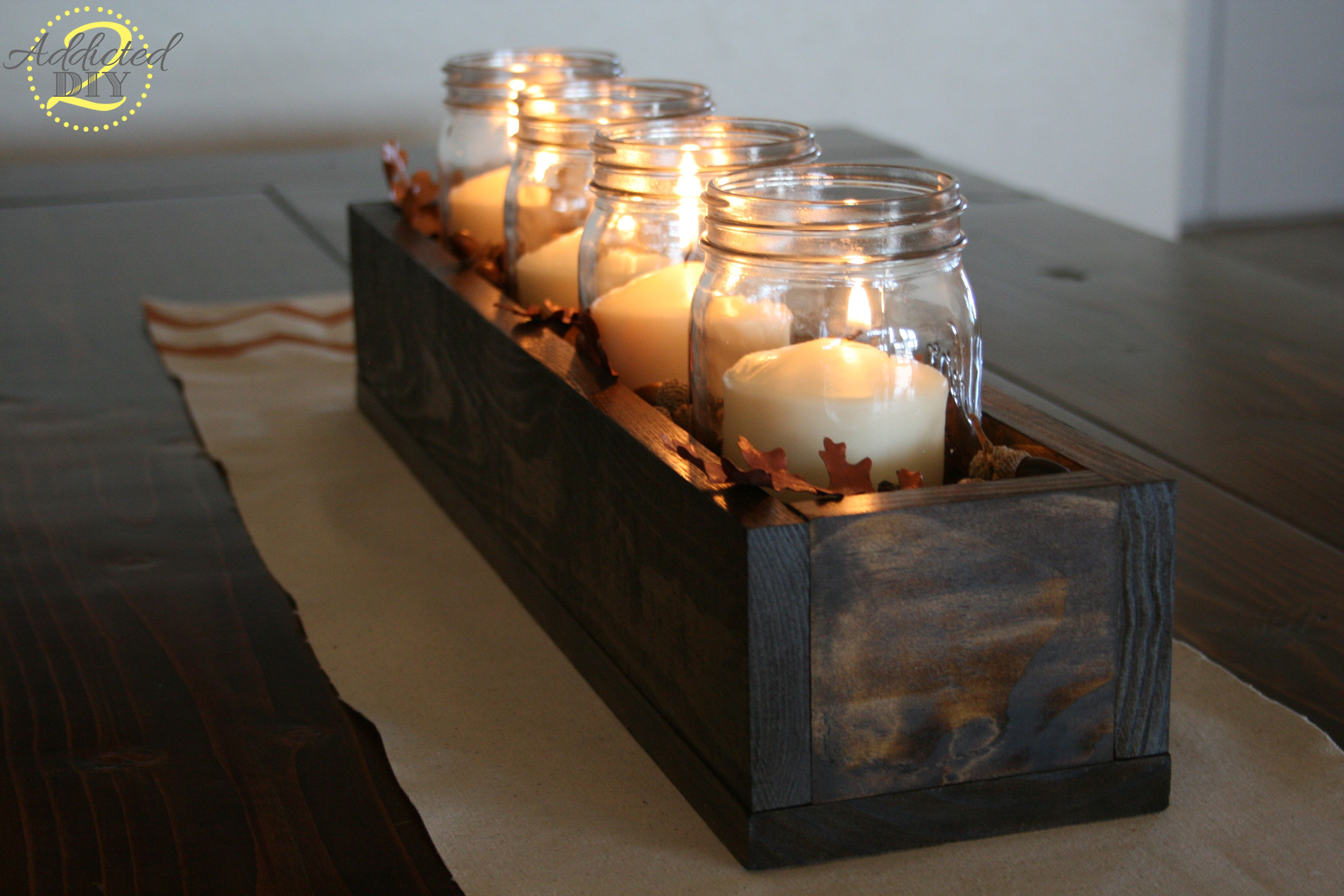 A DIY Mason Jar Candle Centerpiece Tutorial. Decorate with a fresh take on mason jar decor. The dark wood with fall leaf accents and a chevron runner are just the perfect fall touch!