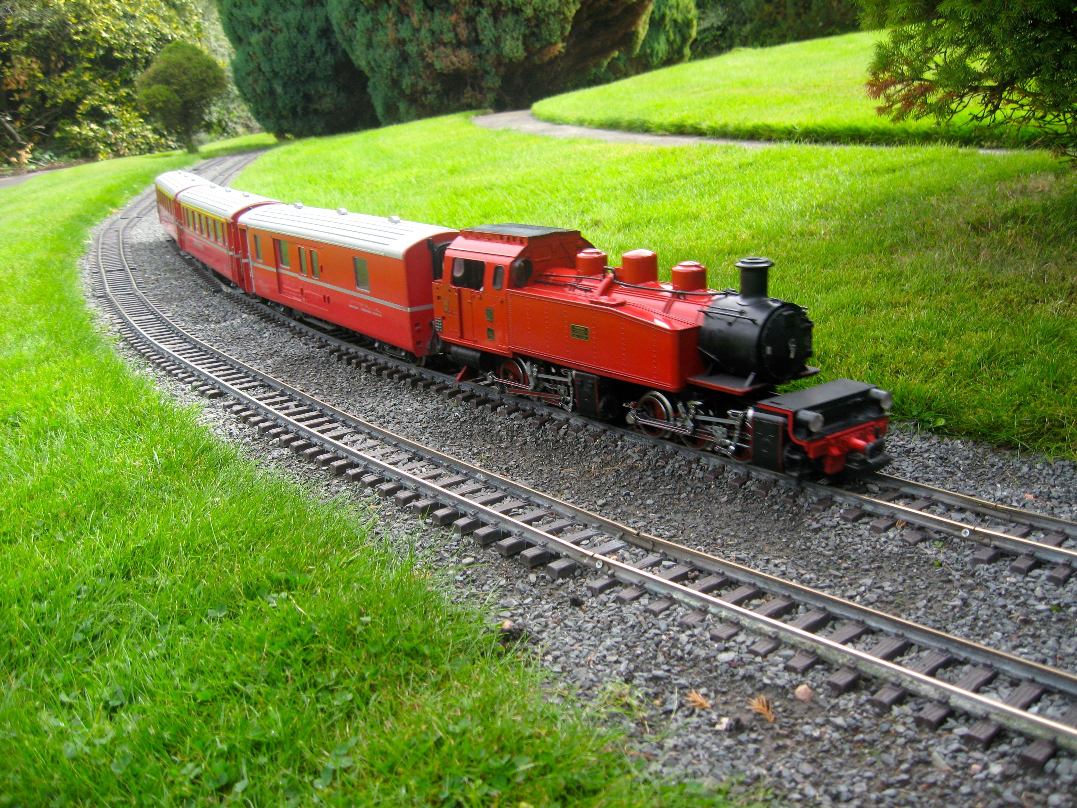Red engine meanders through the countryside scene at ...