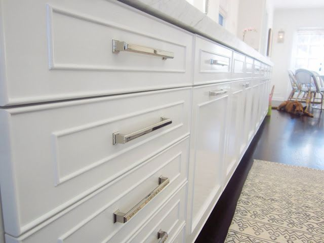 Close up of white panel cabinets with polished nickel drawer pulls ...