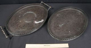 VINTAGE OVAL-SHAPED TRAYS MADE OF WOOD AND COPPER WITH A BLACK PATINA FINISH AND ORNATE INLAYED DETAILS. ONE TRAY MEASURES 16 IN. X 12 IN. THE OTHER TRAY MEASURES THE SAME, BUT HAS METAL HANDLES.