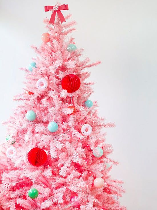 Start with a brightly colored tree for a sweet-as-can-be look. Ornaments include 3-D red paper balls and basic bulbs in pastel colors. Extra sweetness is achieved through a peppermint-dotted bow topper and homemade doughnut ornaments. The doughnuts were made with plaster in a standard doughnut-baking mold. (image credit: Kelly Lanza)/
