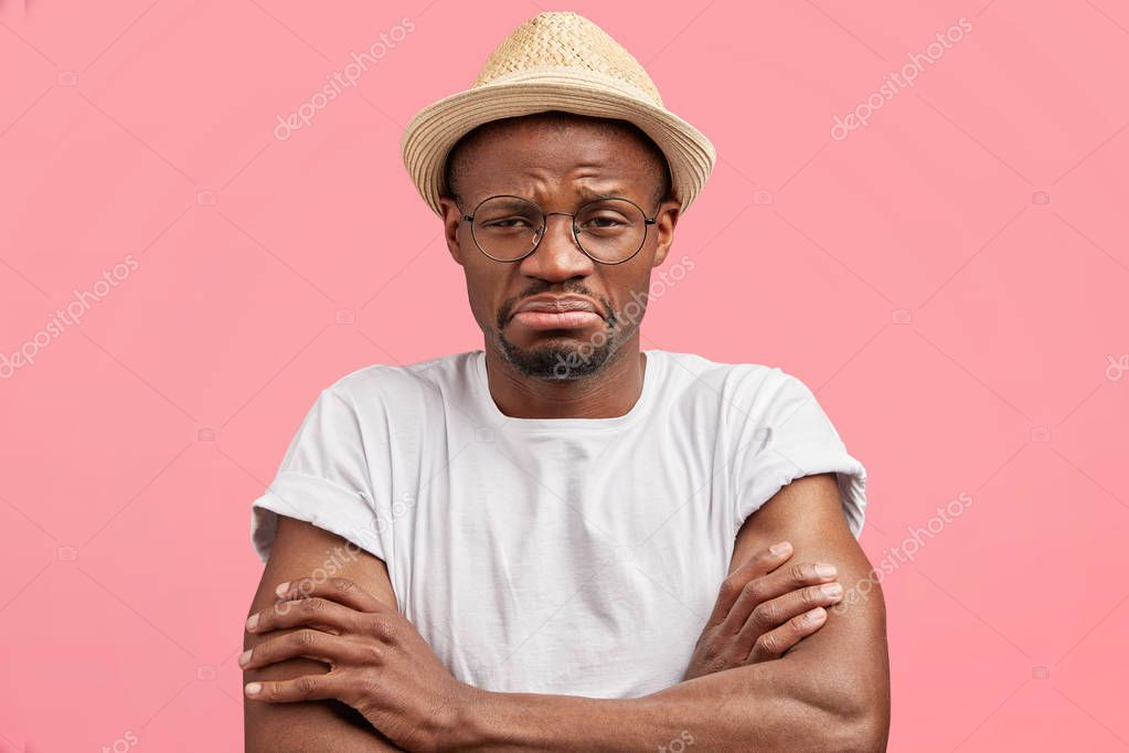 Headshot bored african american male keeps arms folded