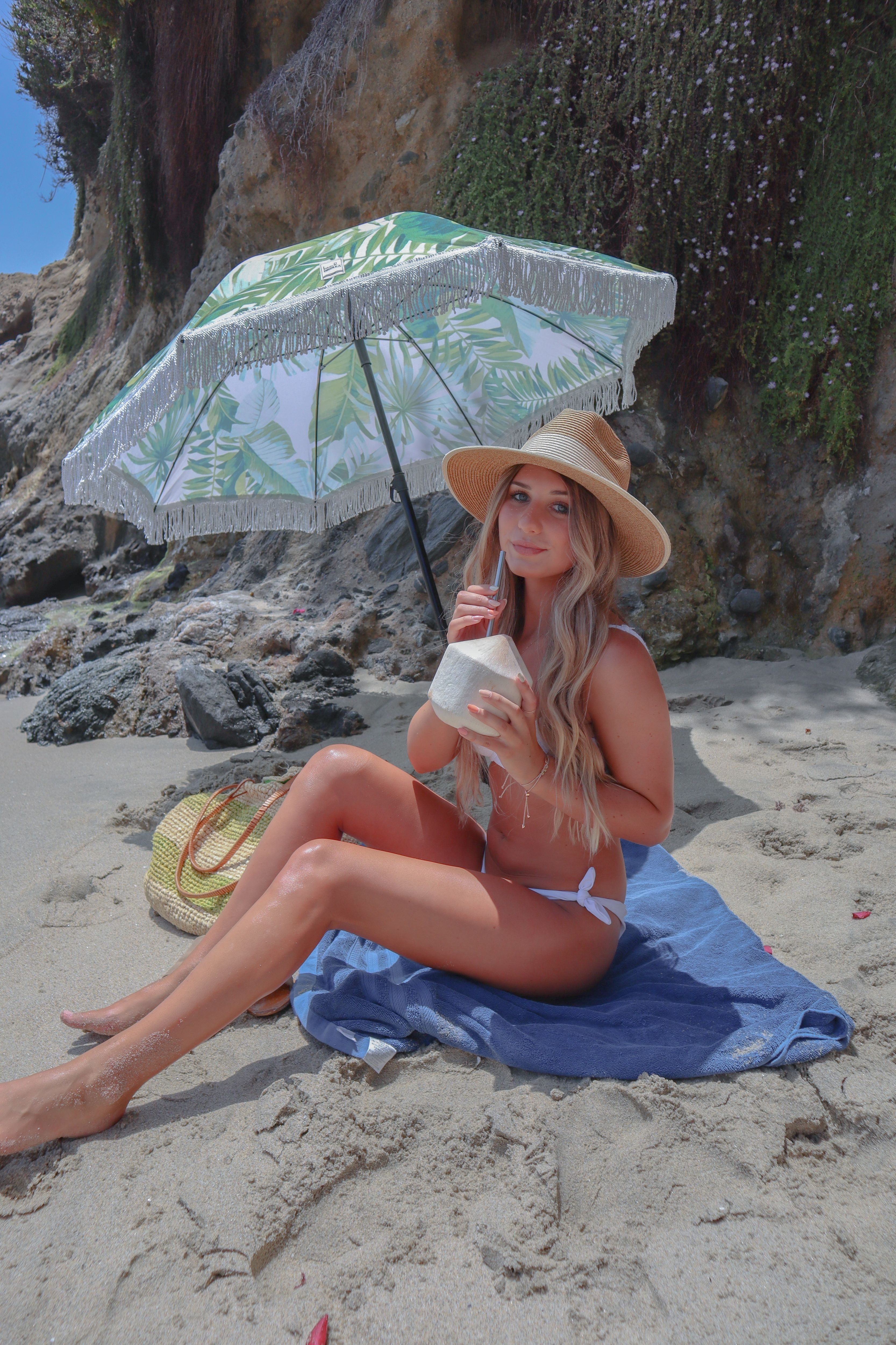 Cute palm beach umbrella with a cute girl drinking her coconut water for earth day. .