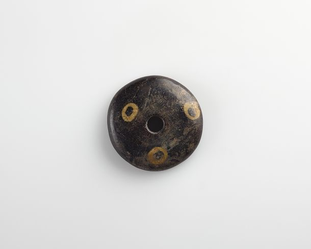 Click to zoom Disk bead amulet Medium: Glass Dimensions: Diam (overall): 3.4 cm (1 5/16 in) Type: Glass Origin: Syria Topic: Syria, Ancient Near Eastern Art, protection Credit Line: Gift of Charles Lang Freer Date: 4th century