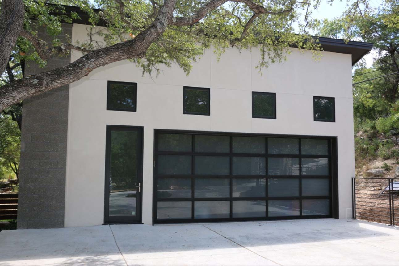 beautiful detached garage design. two car garage. fat metal roof. white stucco siding veneer. black and glass garage doors. contemporary style.