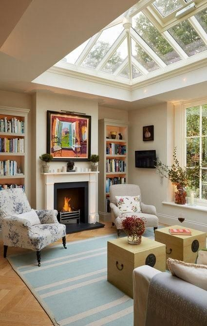 Lounge room within orangery featuring fireplace #livingroomdesigns