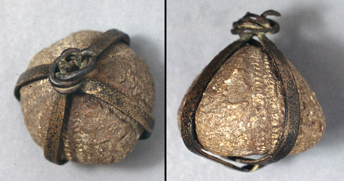 "Viking jewelry / amulet, sea urchins fossil with bronze ""thread"" from Lindholm, Noerresundby, in Denmark"
