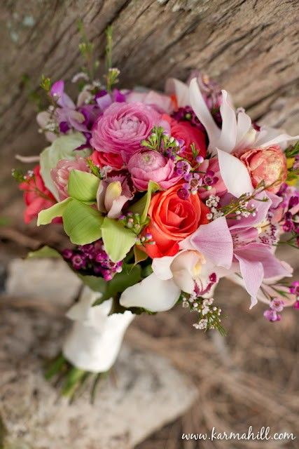 Pink ranunculus.  Pink roses.  Pink lilies.  Green orchids.  Purple waxflower