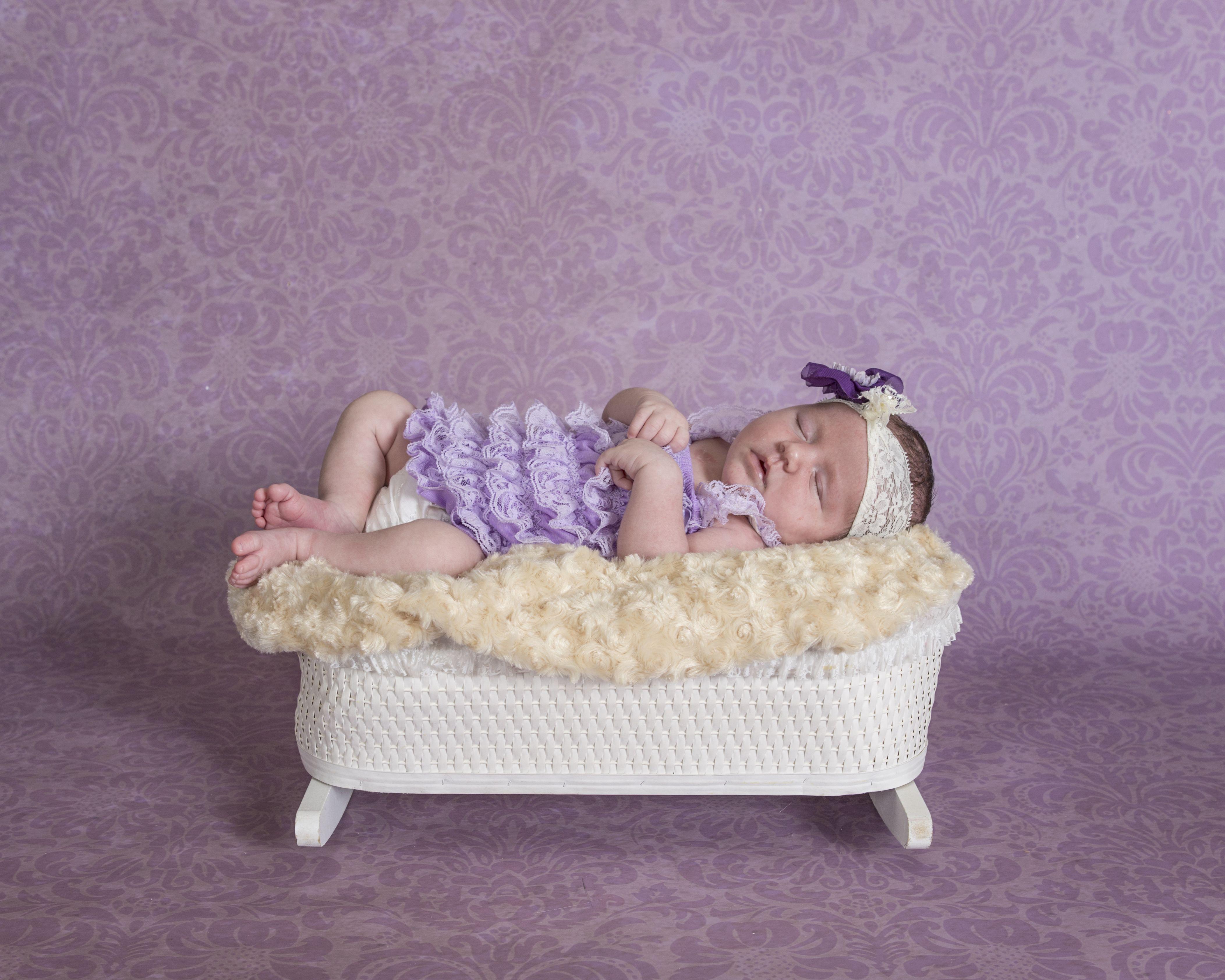 newborn girl in purple lace romper in vintage crib