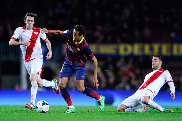 Neymar of FC Barcelona duels for the ball with Raul Baena (L) and Ruben Rochina of Rayo Vallecano to score his team's sixth goal during the La Liga match between FC Barcelona and Rayo Vallecano de Madrid at Camp Nou on February 15, 2014 in Barcelona, Catalonia.